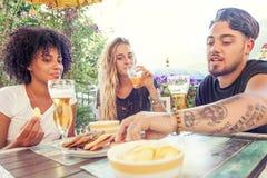 Groupe de jeunes amis mangeant des casse-croûte et le boire Photos stock