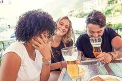 Groupe de jeunes amis mangeant des casse-croûte et le boire Photo stock