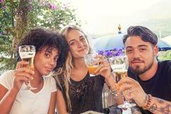 Groupe de jeunes amis mangeant des casse-croûte et le boire Image libre de droits