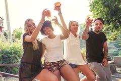 Groupe de jeunes amis mangeant des casse-croûte et le boire Images libres de droits