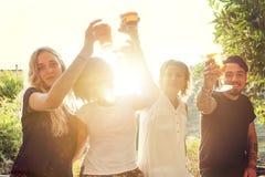 Groupe de jeunes amis mangeant des casse-croûte et le boire Photographie stock