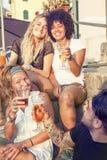 Groupe de jeunes amis mangeant des casse-croûte et le boire Photographie stock libre de droits