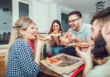 Groupe de jeunes amis mangeant de la pizza Photo stock
