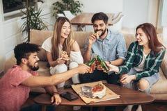 Groupe de jeunes amis mangeant de la pizza Image stock