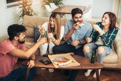 Groupe de jeunes amis mangeant de la pizza Image libre de droits