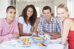Groupe de jeunes amis mangeant le repas à la maison Images libres de droits