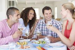 Groupe de jeunes amis mangeant le repas à la maison Images stock