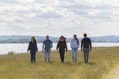 Groupe de jeunes amis marchant sur la colline sur la rivière large de fond Photos libres de droits