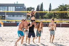 Groupe de jeunes amis marchant sur la cour de volleyball de plage photographie stock libre de droits