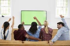 Groupe de jeunes amis observant des sports à la télévision et au Cheerin Image libre de droits