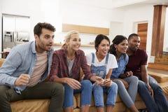 Groupe de jeunes amis observant des sports à la télévision et au Cheerin Images libres de droits