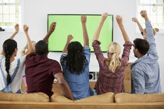 Groupe de jeunes amis observant des sports à la télévision et au Cheerin Photos stock