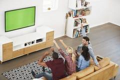 Groupe de jeunes amis observant des sports à la télévision et au Cheerin Photos libres de droits