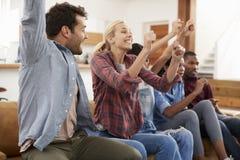 Groupe de jeunes amis observant des sports à la télévision et au Cheerin Photo stock
