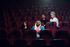 Groupe de jeunes amis observant le film dans le théâtre Photographie stock