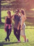 Groupe de jeunes amis posant en parc Photos stock