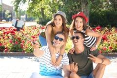 Groupe de jeunes amis prenant le selfie avec le monopod dehors Images libres de droits