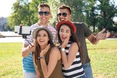 Groupe de jeunes amis prenant le selfie avec le monopod dehors Photographie stock libre de droits
