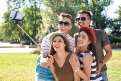 Groupe de jeunes amis prenant le selfie avec le monopod dehors Photo stock