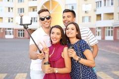 Groupe de jeunes amis prenant le selfie avec le monopod dehors Photo libre de droits