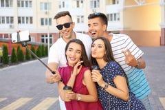 Groupe de jeunes amis prenant le selfie avec le monopod dehors Images stock