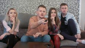 Groupe de jeunes amis regardant la télévision ensemble sur le divan à la maison Photos stock