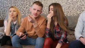 Groupe de jeunes amis regardant la télévision ensemble sur le divan, communiquant, utilisant des téléphones portables Photos libres de droits