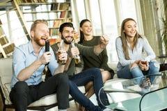 Groupe de jeunes amis regardant la TV Image stock