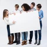 Groupe de jeunes amis regardant un signe vide Images stock