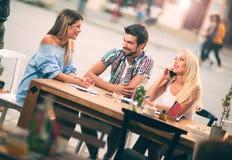 Groupe de jeunes amis riant en café Photographie stock