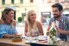 Groupe de jeunes amis riant en café Photos libres de droits