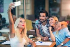 Groupe de jeunes amis riant en café Images stock