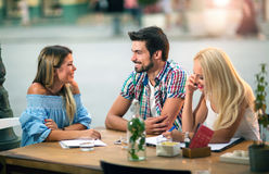 Groupe de jeunes amis riant en café Photographie stock libre de droits