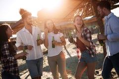 Groupe de jeunes amis riant et buvant de la bière Photos stock