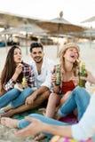 Groupe de jeunes amis riant et buvant de la bière Photo stock