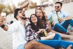 Groupe de jeunes amis riant et buvant de la bière Photographie stock