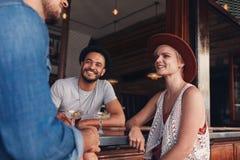 Groupe de jeunes amis s'asseyant et parlant à un café Image libre de droits