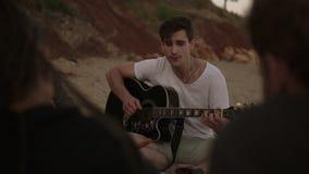 Groupe de jeunes amis s'asseyant par le feu sur la plage, grillant des saucisses et jouant la guitare Tir au ralenti banque de vidéos