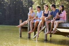 Groupe de jeunes amis s'asseyant sur la jetée en bois regardant au-dessus du lac Photographie stock libre de droits