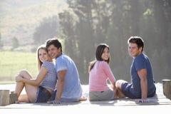 Groupe de jeunes amis s'asseyant sur la jetée en bois regardant au-dessus du lac Photos stock