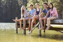 Groupe de jeunes amis s'asseyant sur la jetée en bois regardant au-dessus du lac Image libre de droits