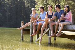 Groupe de jeunes amis s'asseyant sur la jetée en bois regardant au-dessus du lac Photo libre de droits