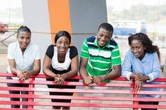 Groupe de jeunes amis se penchant sur un banc Image stock