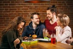 Groupe de jeunes amis se réunissant en café Photos stock