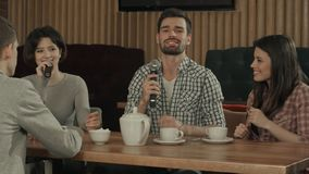 Groupe de jeunes amis sur la partie chantant au club de karaoke Image libre de droits