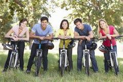 Groupe de jeunes amis sur le tour de cycle dans la campagne Image libre de droits