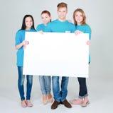 Groupe de jeunes amis tenant un conseil vide, d'isolement sur le fond blanc Images libres de droits