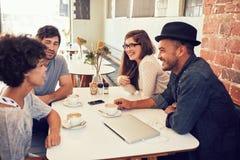 Groupe de jeunes amis traînant à un café Photographie stock libre de droits