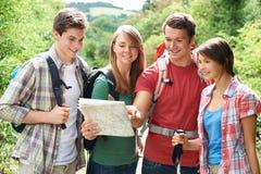Groupe de jeunes amis trimardant dans la campagne Photographie stock libre de droits