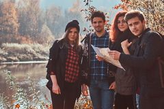 Groupe de jeunes amis trimardant dans la forêt colorée d'automne, regardant la carte et prévoyant la hausse photos libres de droits
